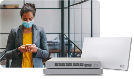 Woman wearing face mask looking down at iphone with Meraki hardware images in foreground