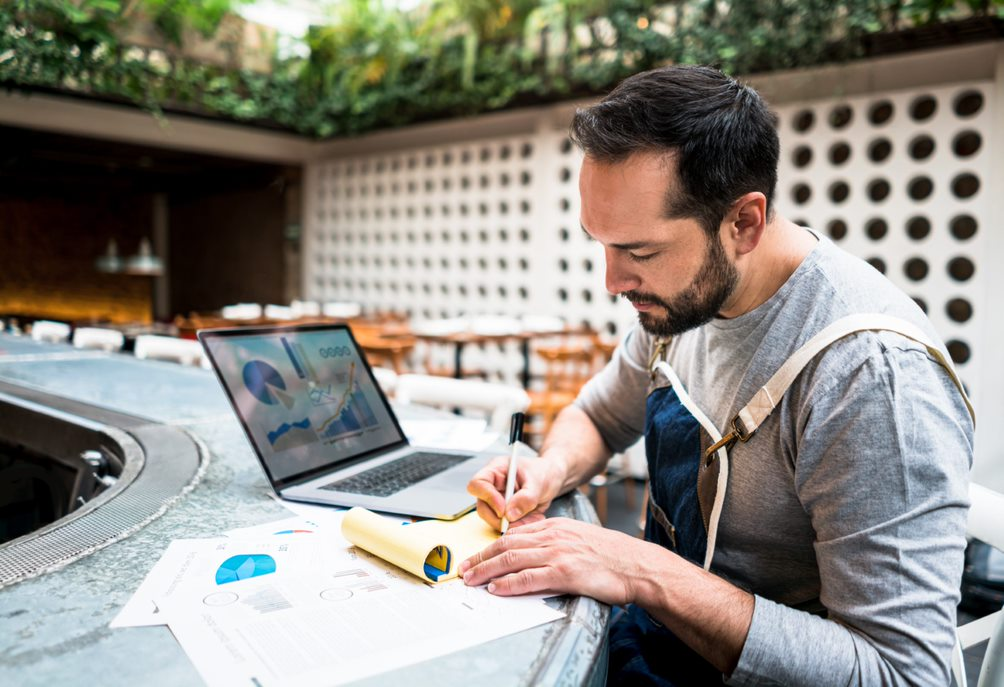 Man sitting at counter with laptop writing on notepad