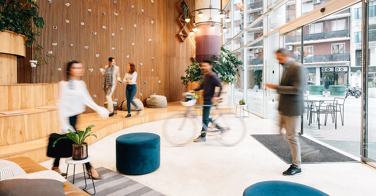 various people walking through an office lobby