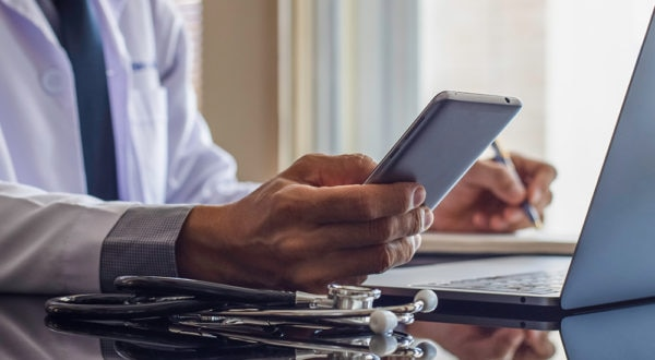Doctor with stethescope sitting in front of laptop while using mobile phone and writing on paper