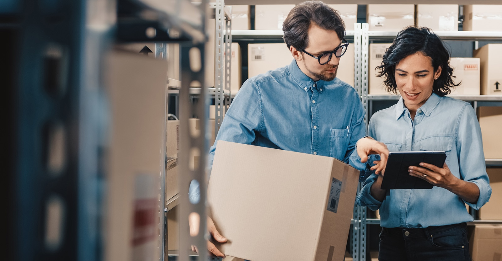 Woman in warehouse with iPad consulting with man carrying box