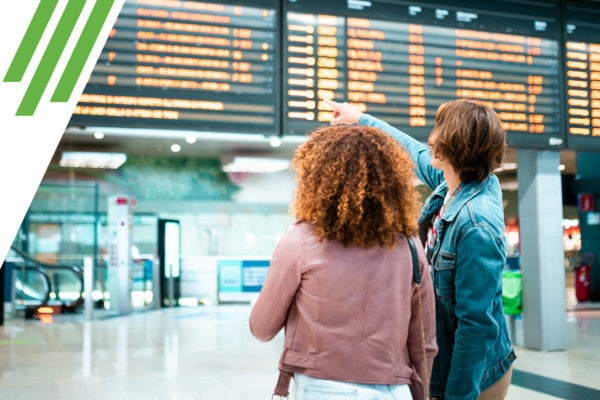 Two women at train station, one pointing at departure board