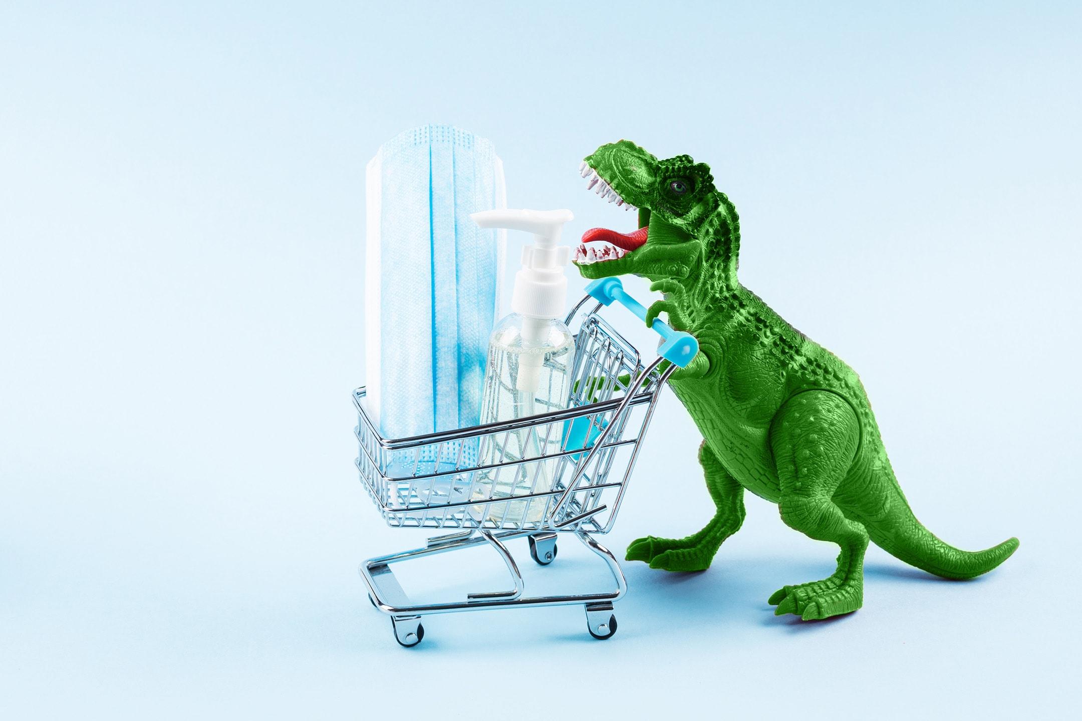 Dinosaurio de juguete verde empujando el carrito de la compra que contiene desinfectante para manos y mascarilla