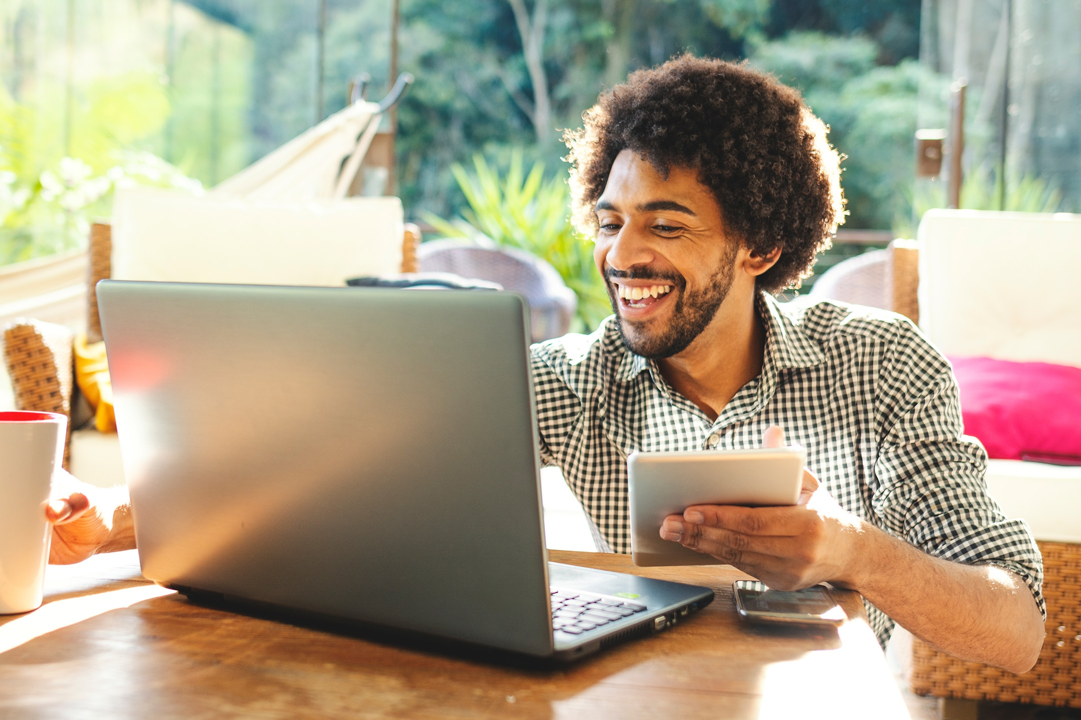 Man working outside on laptop and holding ipad