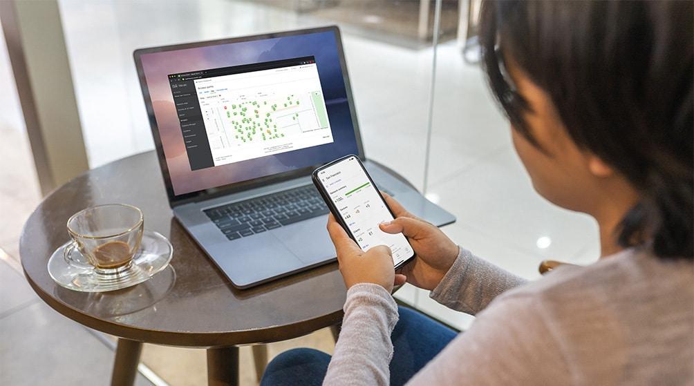 Woman working on Meraki dashboard on a laptop and mobile phone