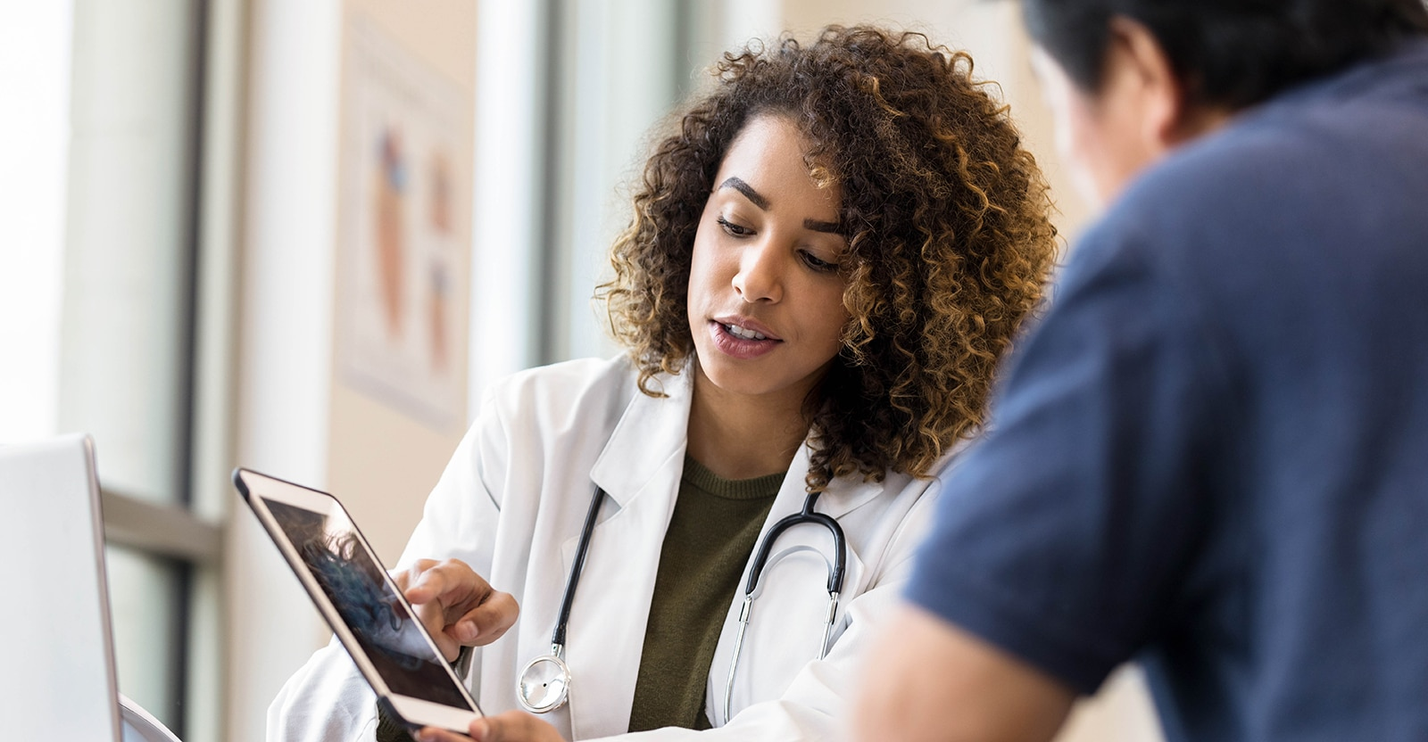 Female Doctor consulting with male patient over iPad