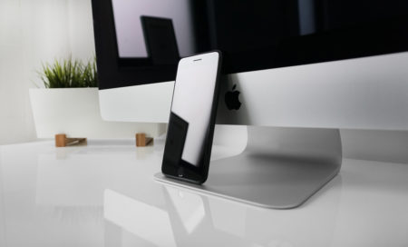 Black iPhone propped up against iMac monitor