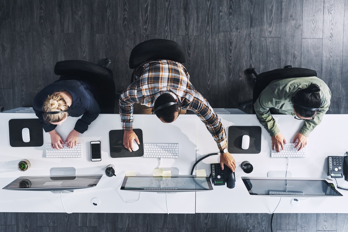 overhead view of three call center workers at their computers