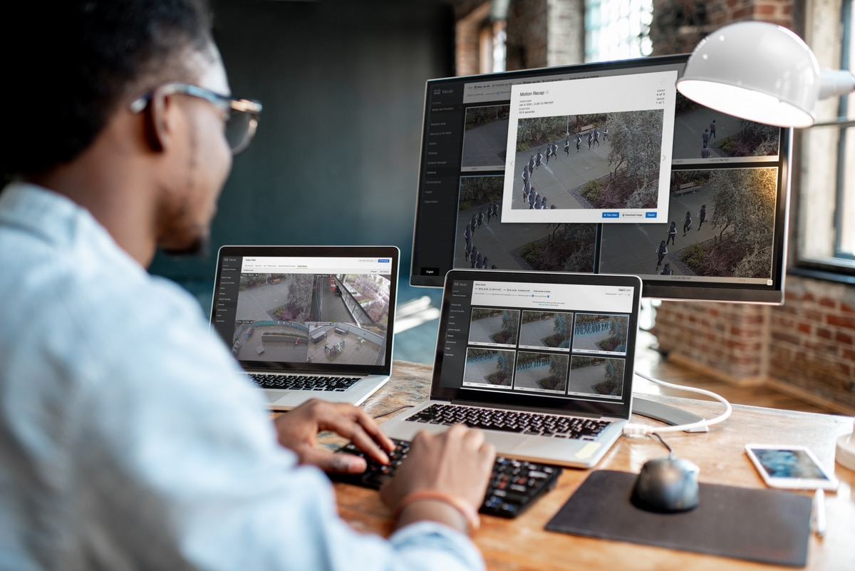 Man at desk viewing security footage on multiple monitors