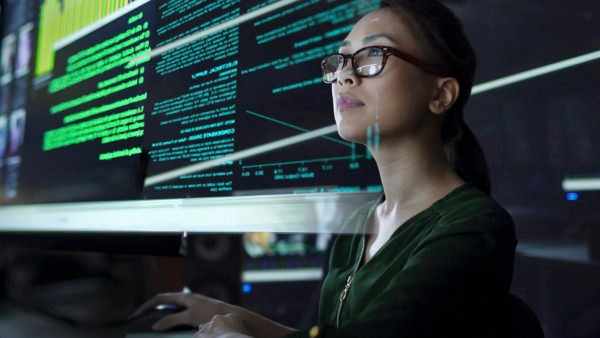 Woman with glasses looking at large computer display
