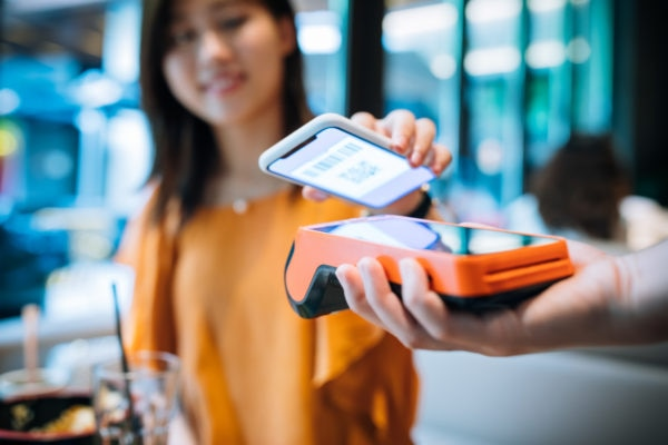 Man holding barcode reader while woman scans phone