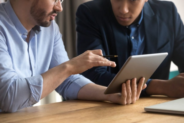Two men collaborating on tablet computer