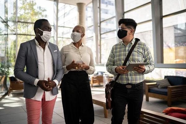 Three people walking in office environment wearing masks