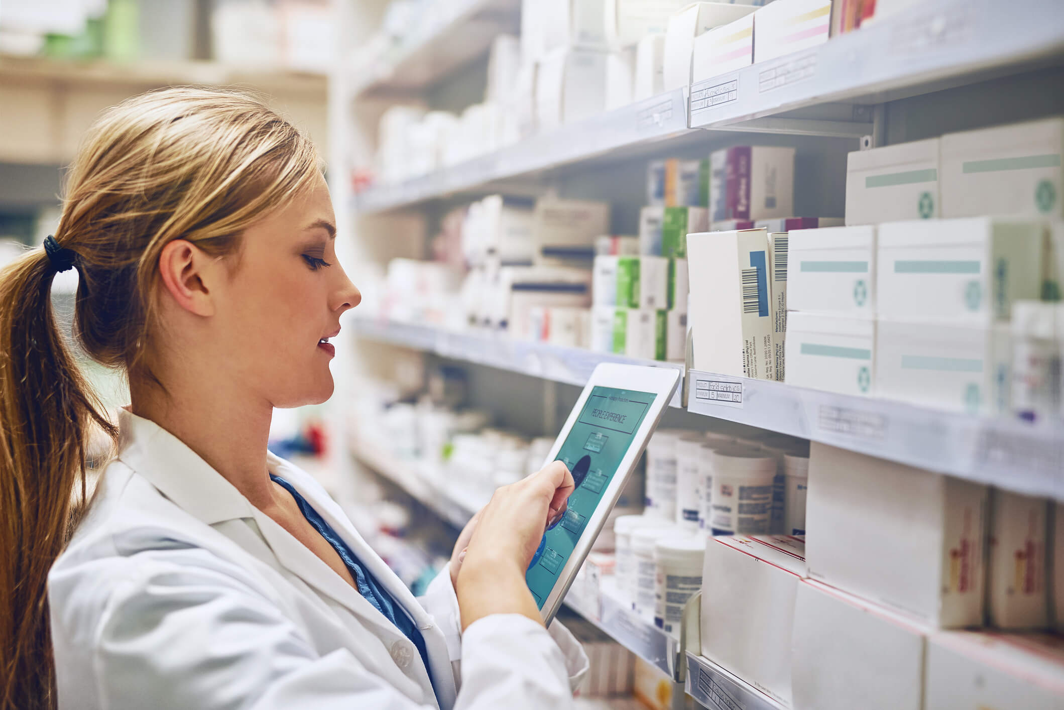 Pharmacy worker checking drug inventory on ipad