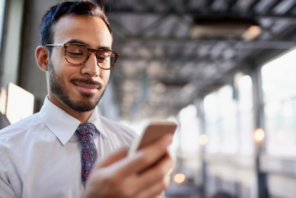 Man in tie and glasses looking at smart phone