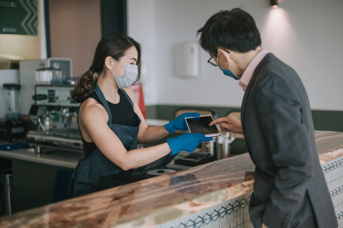 Female cashier consulting with male customer across the counter with ipad
