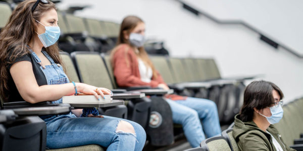 Students sitting in lecture hall wearing masks