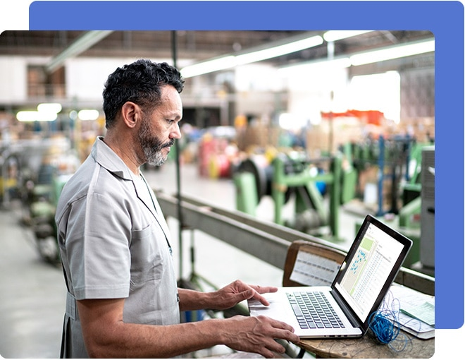 Man in a grey shirt standing in a manufacturing warehouse looking at a laptop computer