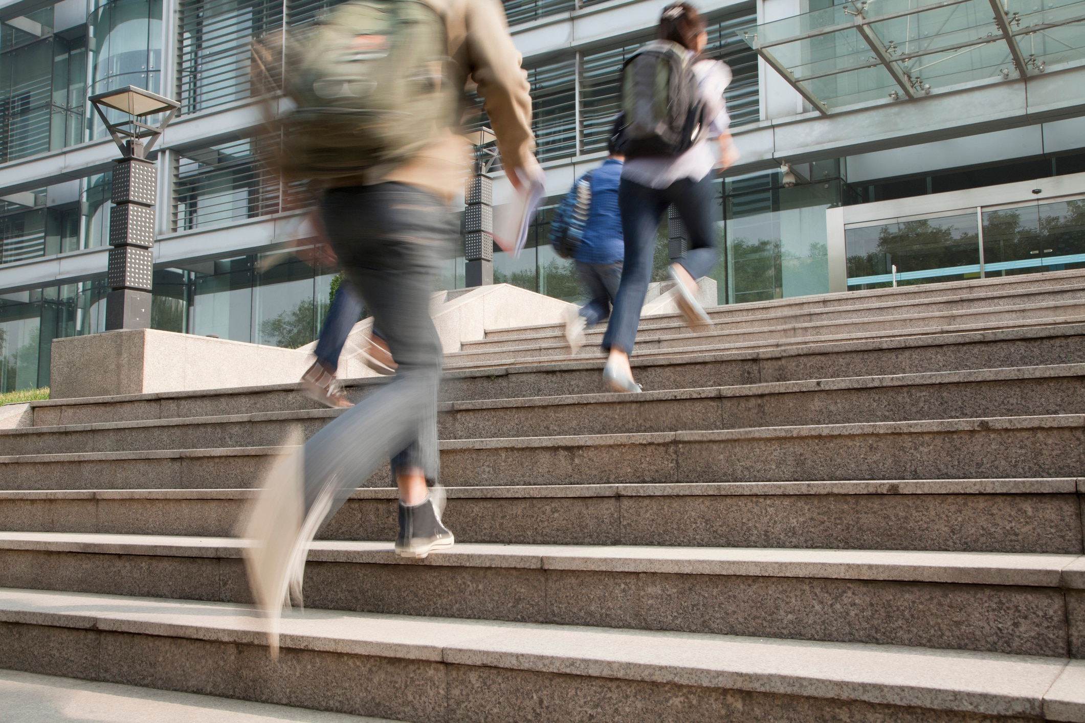 Four people outside running up a flight of stairs