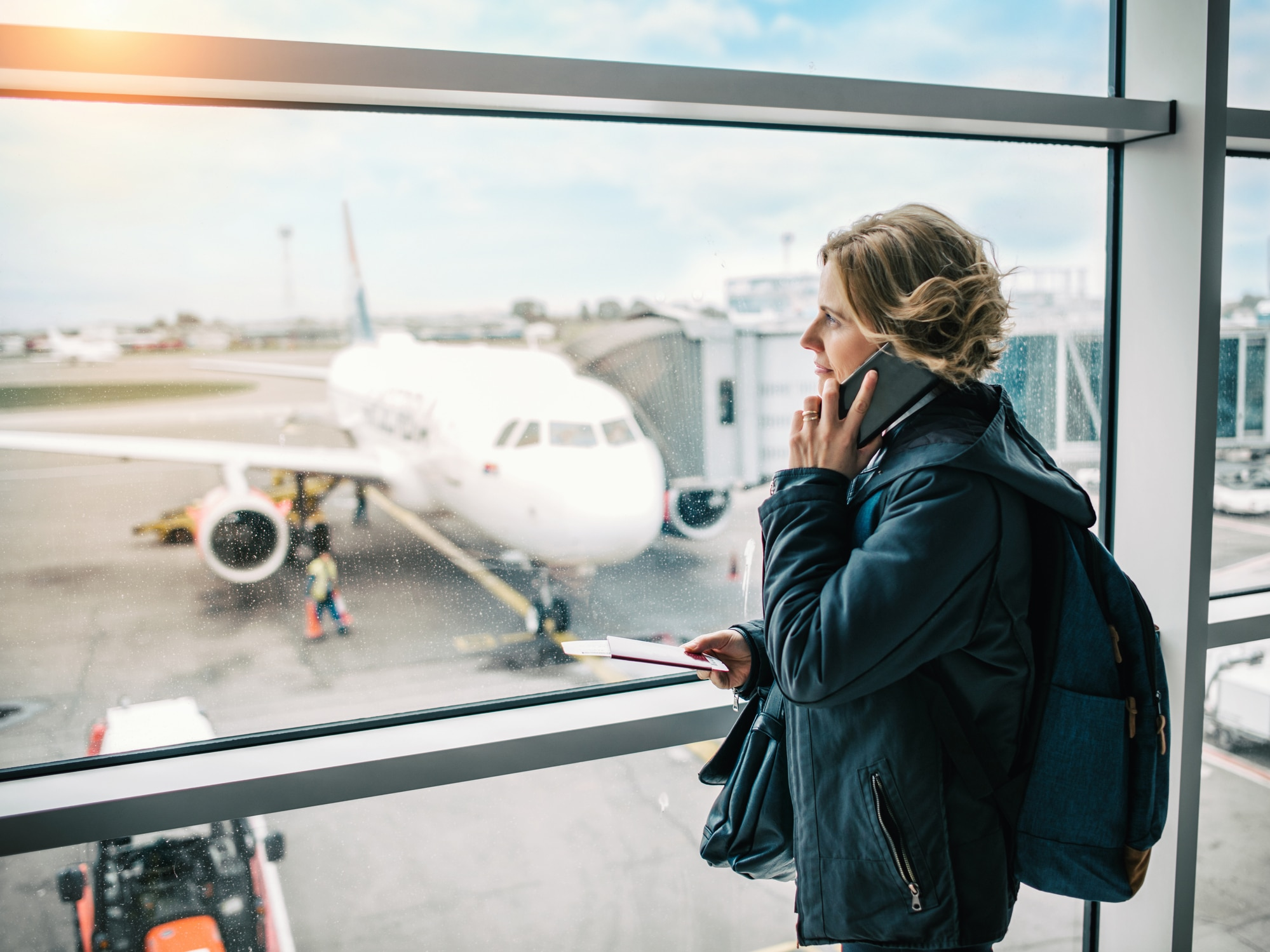 A woman in a green coat on wating for her plain at an airport