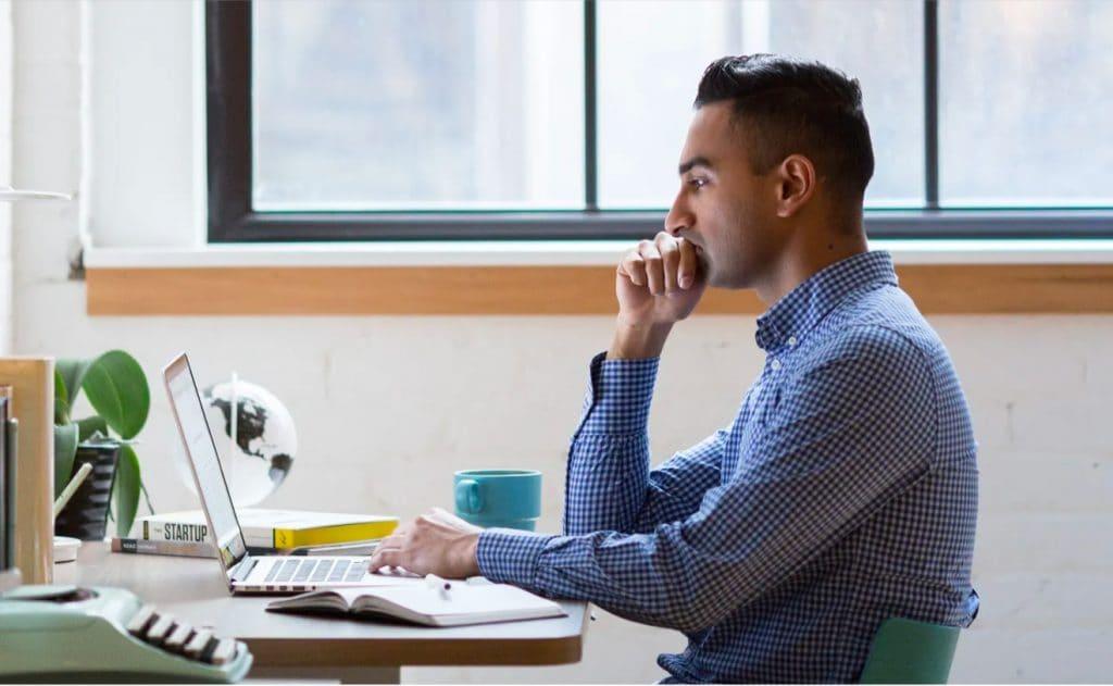 Man in a blue shirt working on a laptop sitting a desk near a window
