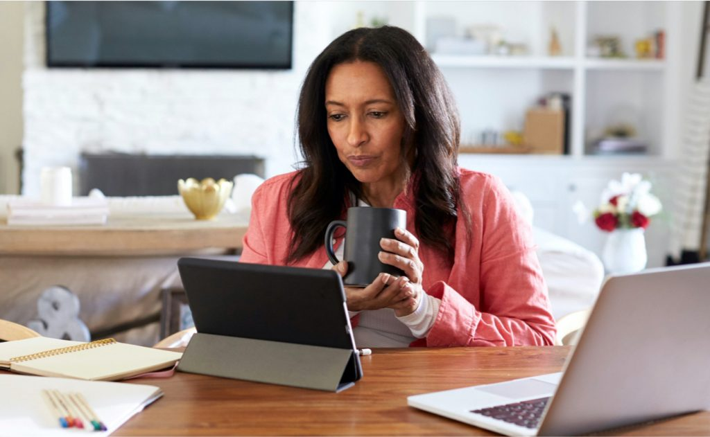 Woman in a peach shirt sitting at a desk holding a cup of coffee looking at a tablet computer